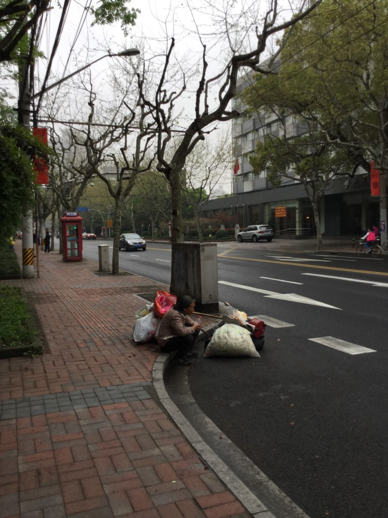 A woman Sits on the corner of the French Concession in Shanghai